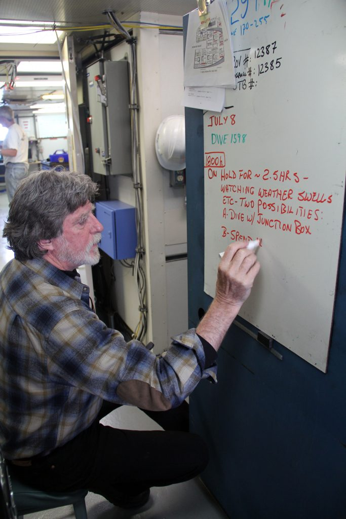 "Chief Scientist, John Delaney, updates the whiteboard that serves as the primary message center. It is affectioately nicknamed ""The Board of Lies"" due to continuously changing and shifting plans at sea. (photo: Allison Fundis)"
