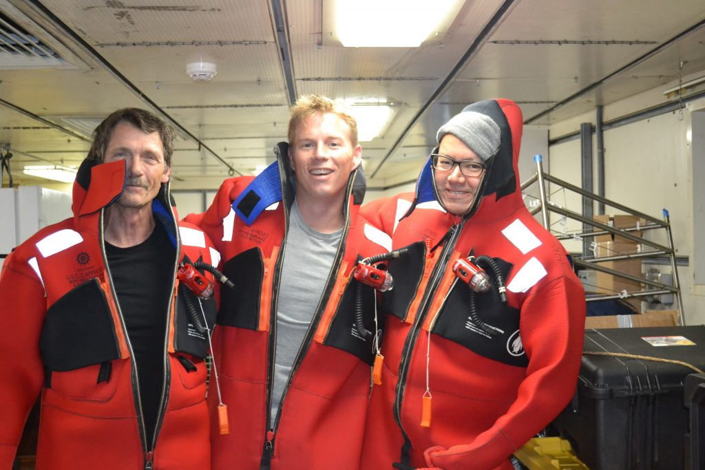 Fire and boat drill aboard the R/V Thompson during Leg 1 of the VISIONS'13 expedition. Steve. Jason, and Jonathan from the ROPOS Team raced to get survival suits on. Photo by M. Elend.