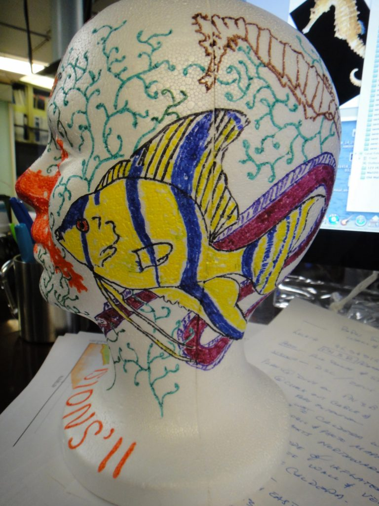 "To highlight the impacts of pressure and for relaxing downtime, it is a common tradition on ROV cruises to color styrofoam heads and cups and take them down to the seafloor. Styrofoam cups come up about 1 inch tall. This head has not yet been ""shrunk"" but will go down in a few days."
