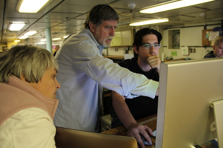 Debbie Kelley, John Kelley, and Alden Denny look over newly acquired EM302 data. (photo by Allison Fundis)