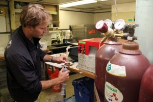 Injecting a gas sample into the gas chromatograph to analyze the concentration of methane. (photo by Allison Fundis)