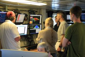 Monitoring the CTD data as the CTD is lowered almost 800 m down in the water column August 14. From left to right: Alden Denny (UW graduate student), Lexi Brewer and Cody Turner (UW undergraduate students), and Orest Kawka and Kendra Daly (OOI-RSN project scientists). (photo by Ed McNichol)