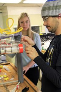 Lexi Brewer, a UW senior, assists Evan Solomon, a UW faculty member and geochemist, prepare his flow meter that will be deployed at Southern Hydrate Ridge. (photo by Allison Fundis)