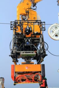 The ROV ROPOS coupled to the Science Interface Assembly as it is being lowered into the water. (photo by Allison Fundis)
