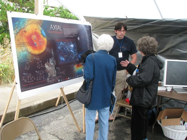 UW graduate student Alden Denny explains the planned cabled network experiments at Axial Seamount to visitors to the OOI booth at the Pacific City Dory Days Festival.  	--Photo courtesy of David Muerdter