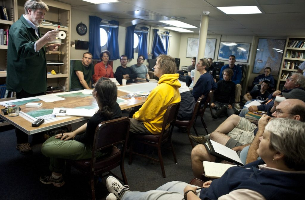 Co-chief Scientist, John Delaney, discusses with the science party the best way to utilize our ship time while the ROV Jason is not in the water due to a little bit of rough weather over the next couple of days. Photo by Carlos Sanchez and Katherine Turner.
