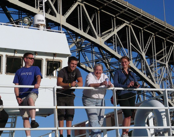 The Thompson passes under the Aurora bridge in Seattle. From left to right, Ed McNichol, Derek Brady, Deb Kelley, and Martha James.