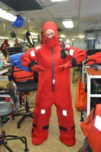 Katie Hill successfully gets into a survival suit during the safety meeting. Credit: M. Elend, University of Washington.