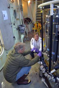 Lauren and Orest sample water from the Niskin bottles. K. Bighman, University of Washington, V19.