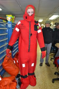 Chris Williams, undergraduate student at UW, dons his survival 'gumby' suit during the day 1 safety briefing for new Leg 3 personnel. Credit: M. Elend, University of Washington, V19