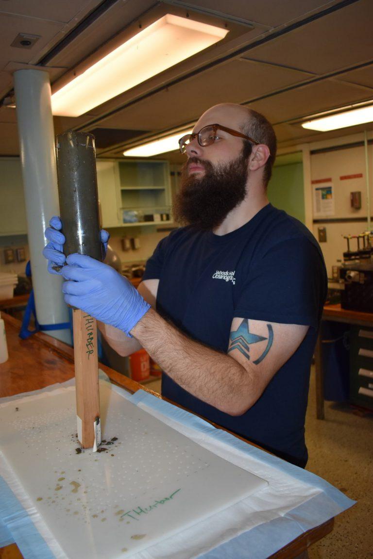 Queens College student, Steve Karaduzovic processes sediment push cores taken at Slope Base during dive J1256. Credit: M. Elend, University of Washignton.