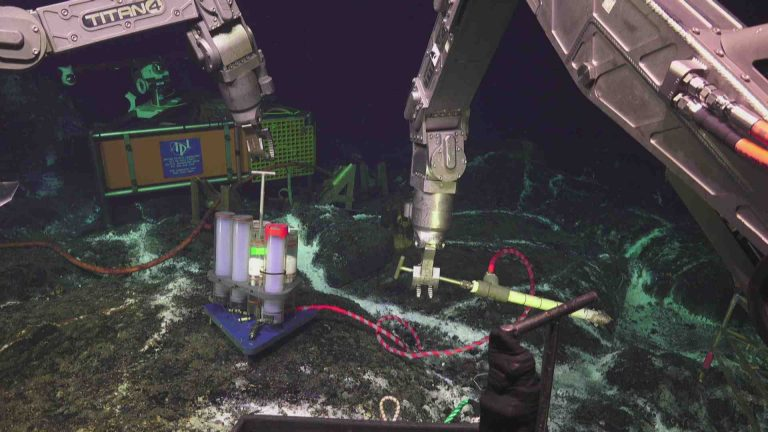 The titan4 arm of Jason reaches for the osmotic fluid sampler in the ASHES hydrothermal field. Fractures in the lobate lava flows leaking warm fluids support colonies of whte bacteria and small tube worms. The HD video camera is in the background. Credit: UW/NSF-OOI/WHOI. V20