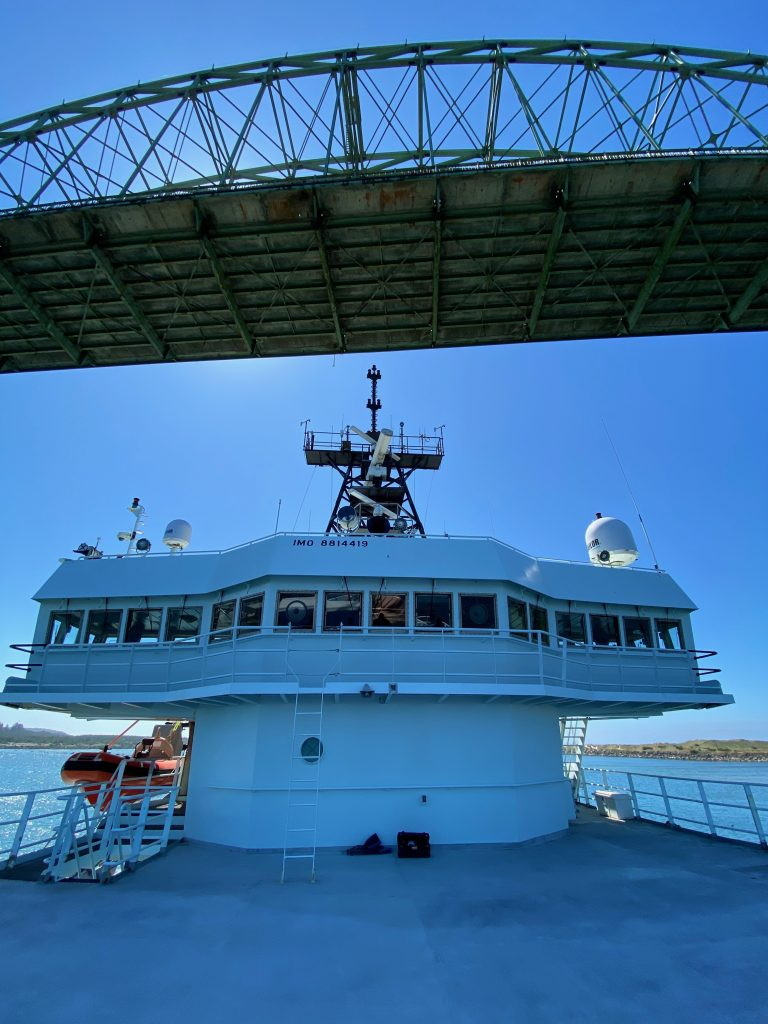 The R/V Thompson is almost in port at the end of the 2020 expedition, here passing under the Yaquina Bay Bridge. Credit: University of Washington, V20.