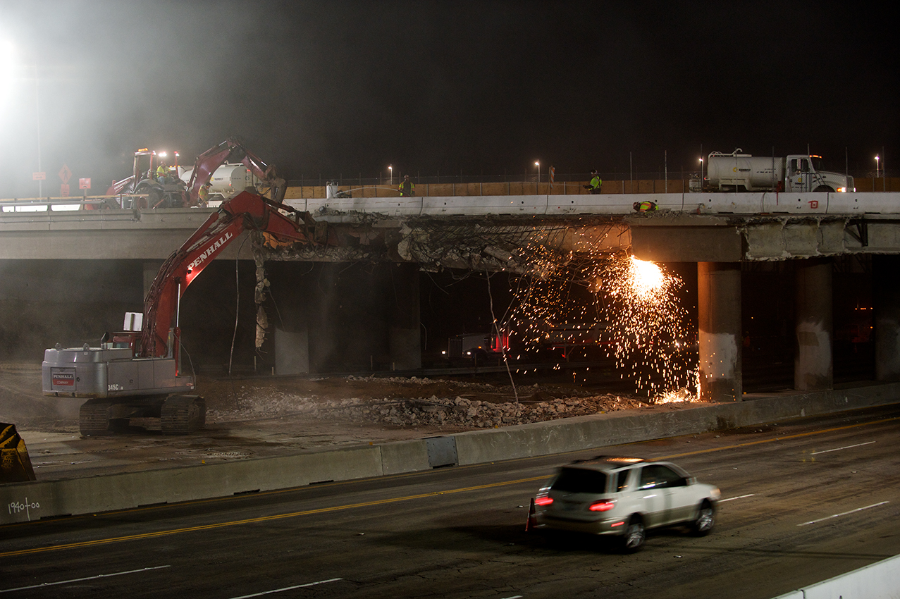 While a vehicle speeds south, the hoe ram punches at the north façade. Water trucks on the bridge spray water on the work area to reduce dust. Concrete from the bridge will be crushed on the project crusher sites and reused in the project. Photo by Peter Watkinson.
