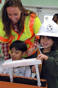 In the interest of safety, Kasey Shuda, Wilshire Segment Community Relations Officer, loans her hard hat to a young bridge engineer.