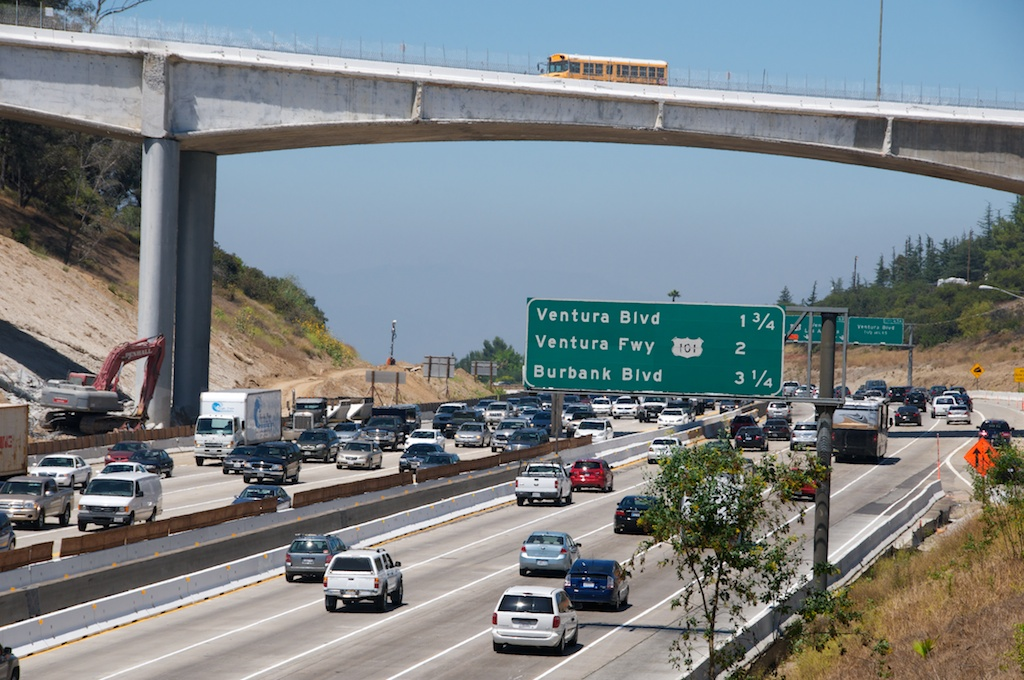 Partial demolition of the Mulholland Bridge stopped traffic on Carmageddon weekend. One week later, a school bus crosses on the remaining half of the Mulholland Bridge as traffic pours under the bridge at the start of rush hour on Friday, July 22. Photos by Gary Leonard