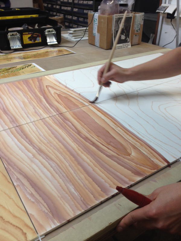 Highly skilled artisans paint a wood likeness onto ceramic tile. Photo Credit: Mayer of Munich