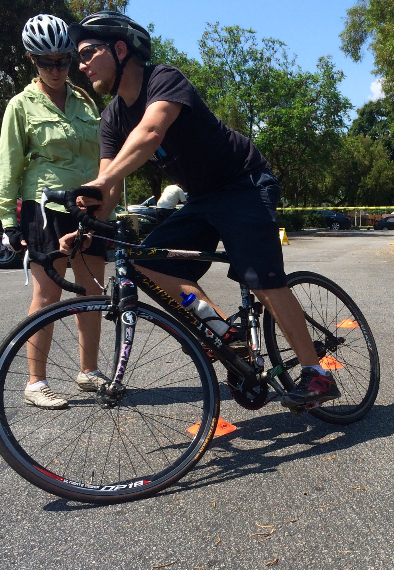 A safety instructor teaches bicycle maneuvering skills on road course.