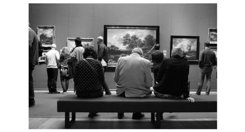 People at a museum sitting or staring at Paintings and admiring the art.