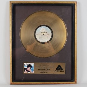 "Offered here is one of the Gold Records awarded from the R.I.A.A. for sales of more than 500,000 copies. Presented to Barry Mayo Jump To It is an album by Aretha Franklin, produced by Luther Vandross and originally released in the summer of 1982. This disc gave Aretha her tenth #1 R&B album - at the time it was the all-time record. It enjoyed a seven-week run at #1 on Billboard '​s R&B albums chart and also reached #23 on Billboard's main album chart. It was hailed as a comeback album, given that it provided Aretha with her first Gold-certified disc and Top 40 song since Sparkle in 1976. This album is currently out of print. The title track, ""Jump To It"", was Aretha's first Pop Top 40 hit since 1976 and her first #1 R&B hit since 1977's ""Break It To Me Gently"". The infectious song was nominated for a Grammy Award. The album itself received an American Music Award for Best Soul Album."