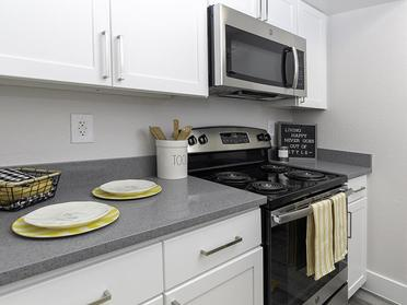 Apartments Salt Lake City, UT - Foothill Place Apartments Fully Equipped Kitchen with Stainless Steel Appliances and White Cabinetry