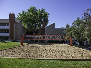 Dog Friendly Apartments in Salt Lake City, UT - Foothill Place Apartments Outdoor Sand Volleyball Court Surrounded by Trees and Well-Manicured Lawn