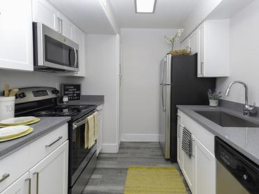 Apartments in Salt Lake City - Foothill Place Apartments Kitchen with Stainless Steel Appliances, Wood Flooring, and White Cabinets