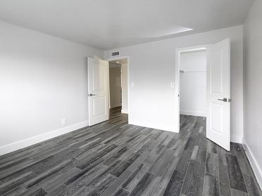 Apartments for Rent in Salt Lake City - Foothill Place Apartments Spacious Bedroom with Gray Wood Flooring and Walk-in Closet