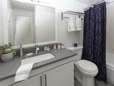 Salt Lake City, UT Apartments for Rent - Foothill Place Apartments Bathroom with a Large Vanity, Stainless Steel Fixtures, and Garden Tub