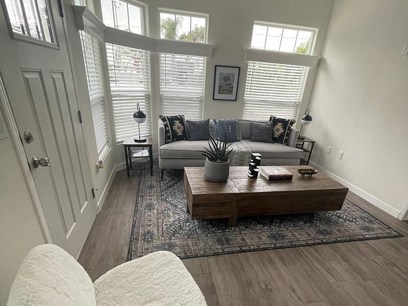 Luxury Apartments in North Hollywood CA - Spacious Living Room With Stylish Gray Wood Flooring and Several Windows for Natural Lighting
