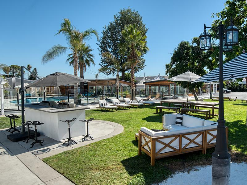 North Hollywood CA Apartments - Outdoor Grill Area with Ample Seating and Lounge Chairs Near Pool Area