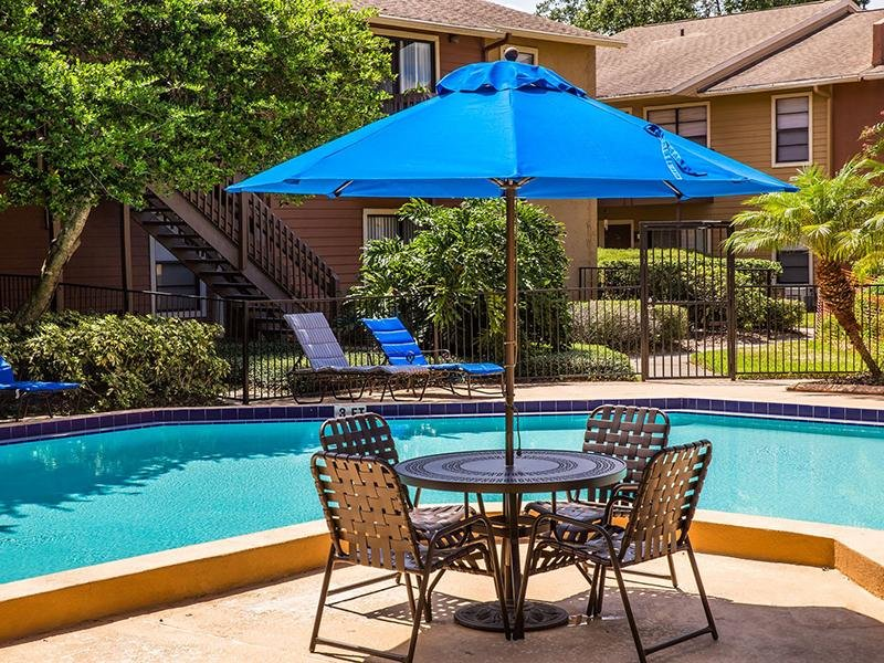 The Swimming pool has a large sun deck with lounge chairs and umbrellas at the Reserve at Conway apartments in Orlando