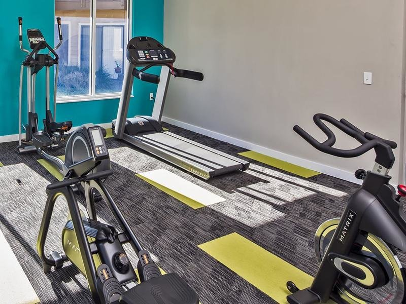 Cardio equipment at Reserve at Conway includes a treadmill, stair machine and spin bike.