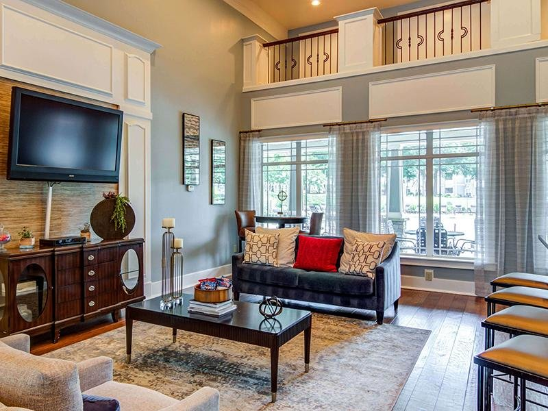 Upholstered couches around a large coffee table in the clubhouse at Eagle's Brooke Apartments in Locust Grove.