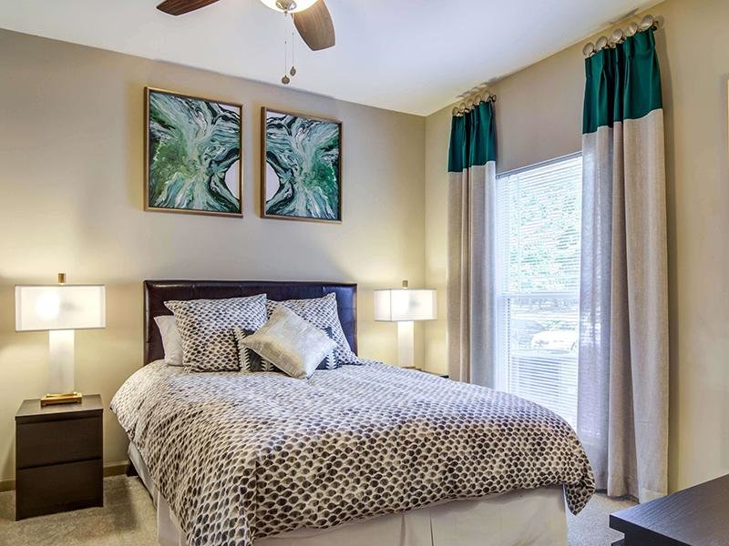 Model bedroom with a large bed and 2 nightstands in the apartments at Eagle's Brooke.