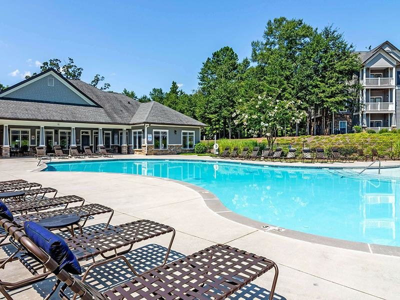 Eagle's Brooke Apartments pool has a sundeck filled with lounge chairs and umbrellas.
