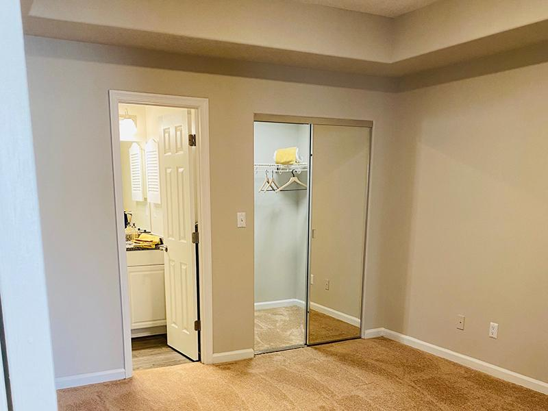A carpeted bedroom with mirrored closet and attached bathroom at The Lakes at Town Center Apartments.