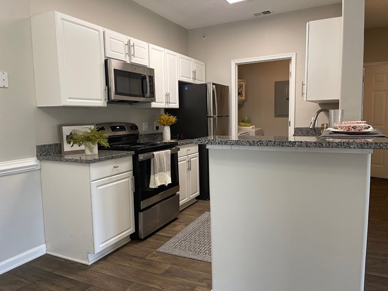 Model kitchen with wood-style flooring and an attached laundry room at The Lakes at Town Center Apartments.