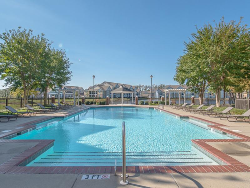 The pool has a sundeck with lounge chairs at The Lakes at Town Center Apartments in Hampton, VA.