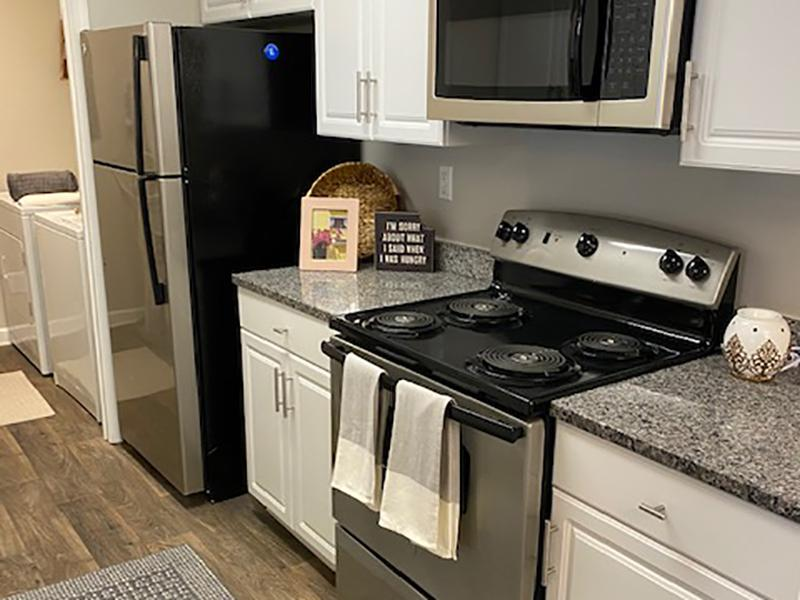 The kitchens at The Lakes at Town Center Apartments in Hampton have wood-style flooring and stainless steel appliances