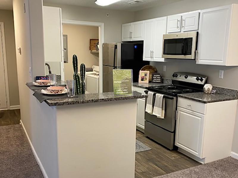 Model kitchen with stainless steel appliances and attached laundry room at The Lakes at Town Center Apartments