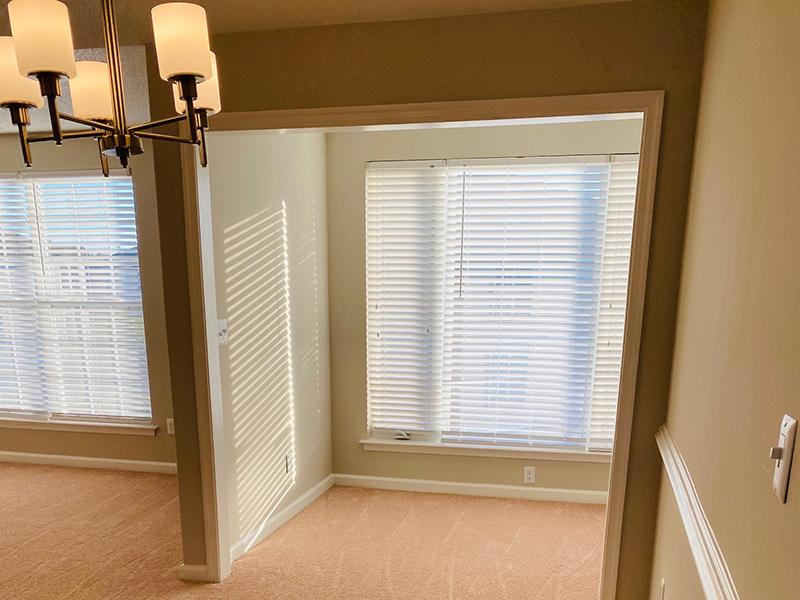 Large windows with blinds in a carpeted room at The Lakes at Town Center Apartments in Hampton.