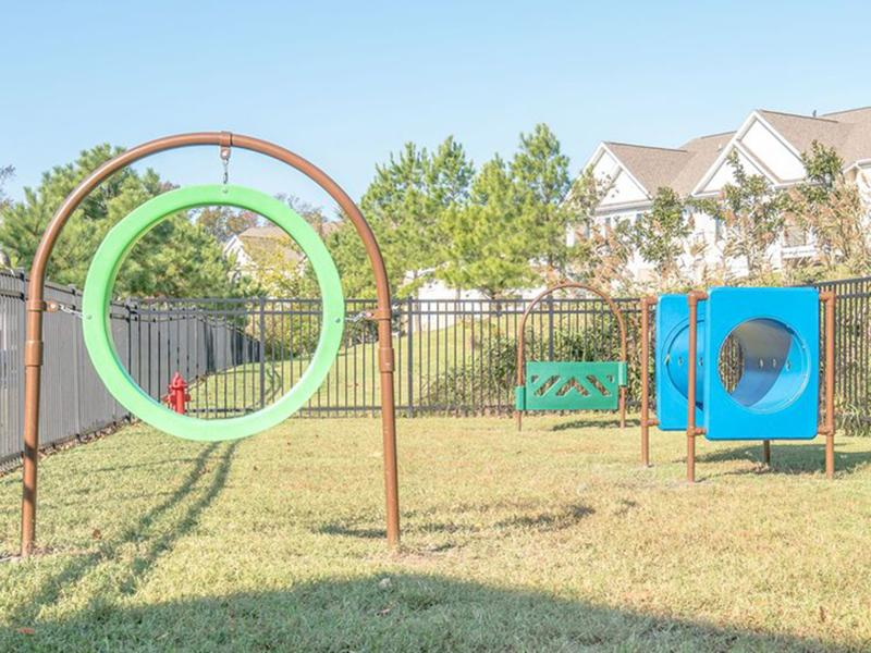 The fenced in bark park has an agility course for your dog at The Lakes at Town Center Apartments.