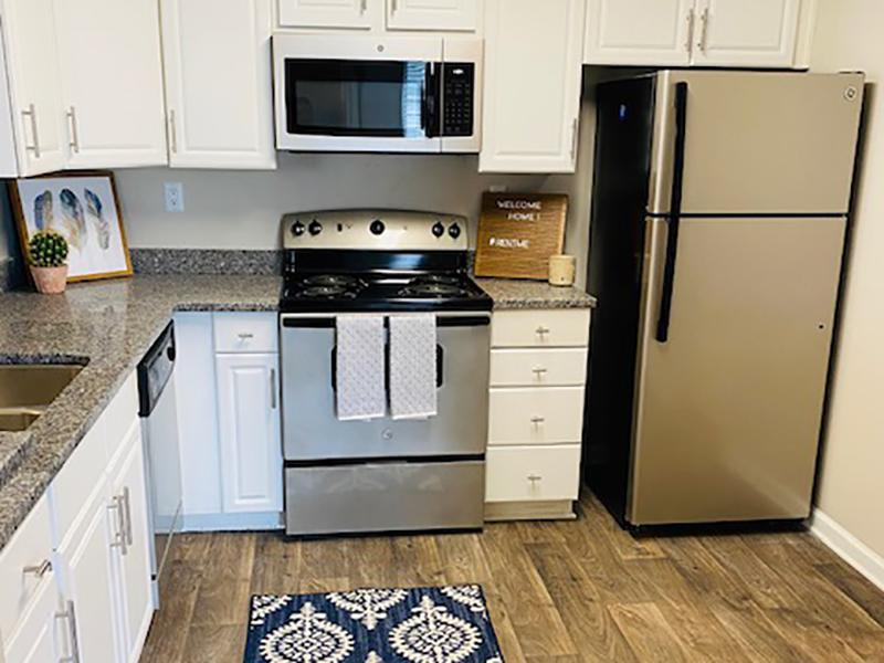 Model kitchen with stainless steel appliances and wood-style flooring at The Lakes at Town Center Apartments