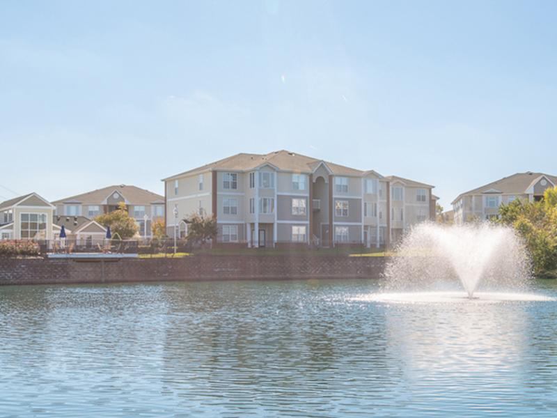 Looking over the community lake with a fountain towards the apartment buildings at The Lakes at Town Center.