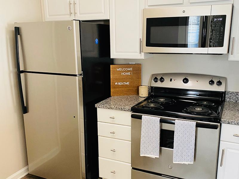 Kitchen with a stainless steel refrigerator and stove at The Lakes at Town Center Apartments in Hampton.