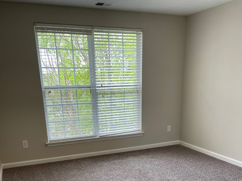 A bedroom with carpet and a large window at The Lakes at Town Center Apartments in Hampton.
