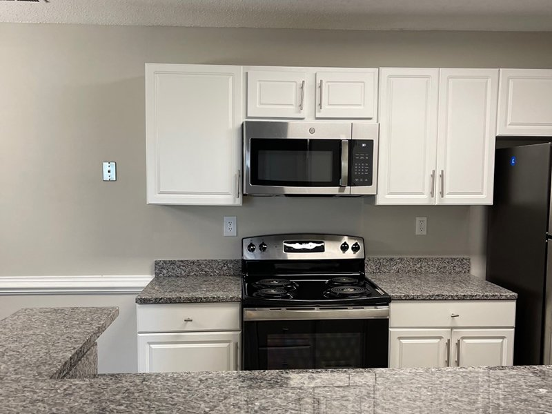 Model kitchen with stainless steel appliances and a breakfast bar at The Lakes at Town Center Apartments.