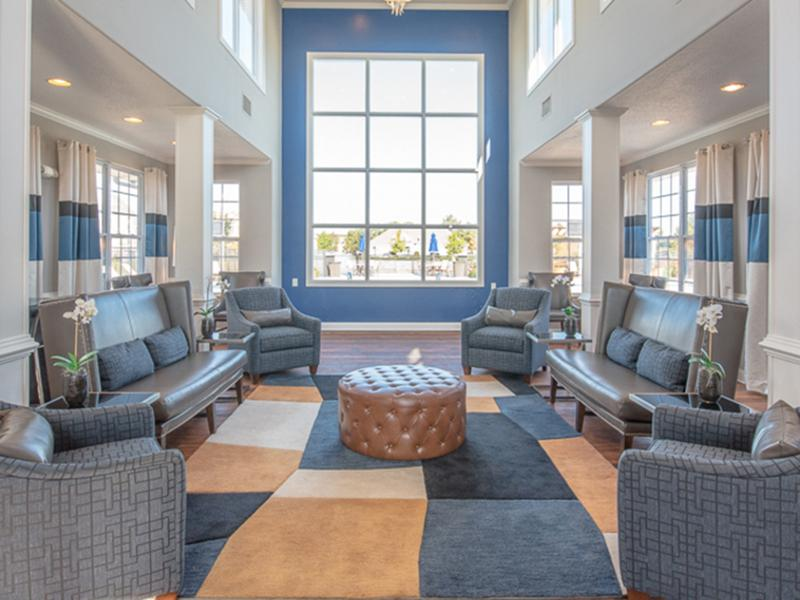 Leather couches and upholstered chairs furnish the lounge at The Lakes at Town Center Apartments.