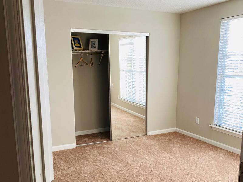 A carpeted bedroom with mirrored closet and windows covered with blinds at The Lakes at Town Center Apartments.